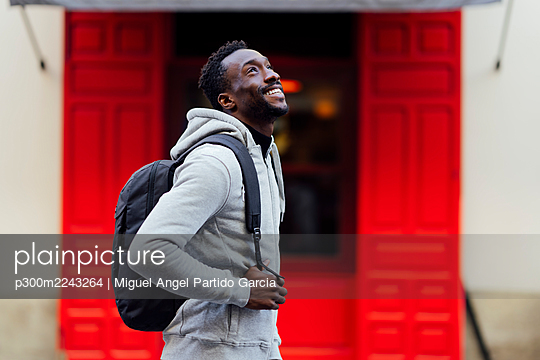 Smiling man hooded shirt looking up while standing outdoors - p300m2243264 by Miguel Angel Partido Garcia