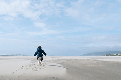 Rear view of girl running on beach against cloudy sky - p1166m1485524 by Cavan Images