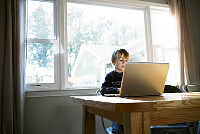 Little boy in morning light sitting at table doing remote school - p1166m2232701 by Cavan Images