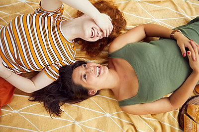 Two young women take a break on a picnic blanket - p1491m2176024 by Jessica Prautzsch
