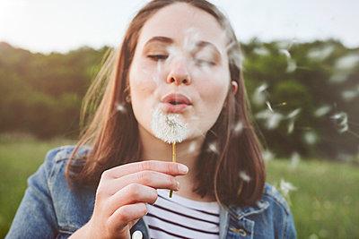 Portrait of teenage girl blowing blowball - p300m2113890 von Annie Hall