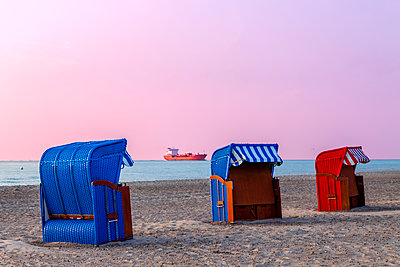 Three hooded beach chairs at sunset, Warnemuende, Rostock, Germany - p300m2114858 by pure.passion.photography
