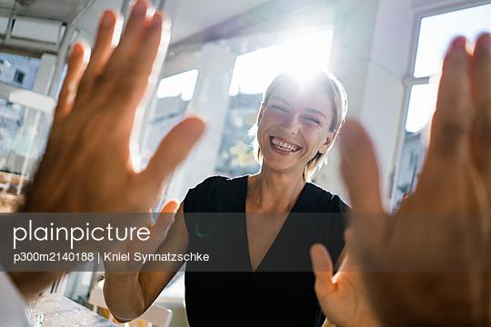 Blond businesswoman high fiving a colleague - p300m2140188 by Kniel Synnatzschke