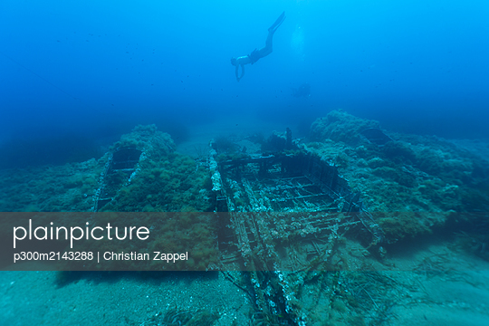Scuba diver swimming toward sunken airplane wreck - p300m2143288 by Christian Zappel