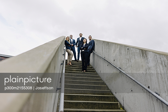 Business people standing on exterior stair looking out - p300m2155308 by Joseffson