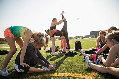 Teenage girl high school cheerleading team stretching on sunny football field - p1192m1500231 by Hero Images