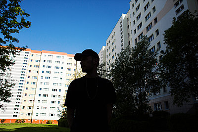 Young man in front of a block of flats - p1301m1582571 by Delia Baum