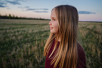 Blond girl looking away in field during sunset - p300m2281741 by Ekaterina Yakunina