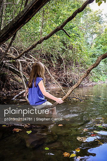 Girl sits on aerial roots on the riverbank - p1019m2124781 by Stephen Carroll
