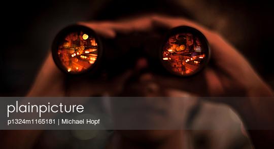 Junger Mann blickt durch ein Fernglas - p1324m1165181 von michaelhopf