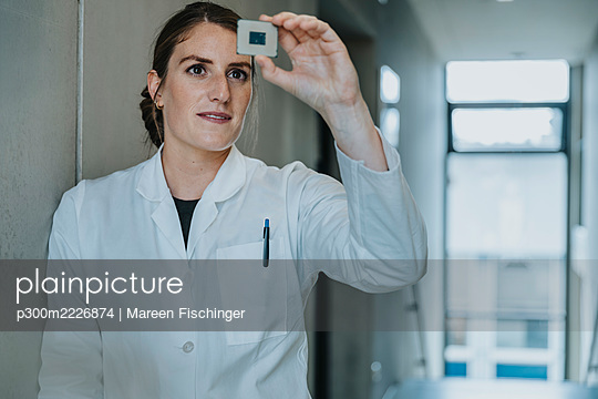 Female scientist holding computer chip while leaning on wall at clinic - p300m2226874 by Mareen Fischinger