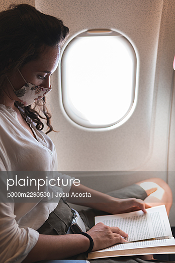 Businesswoman reading book while traveling in airplane during COVID-19 - p300m2293530 by Josu Acosta
