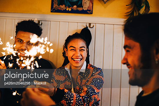Cheerful young multi-ethnic friends sitting with burning sparklers at restaurant - p426m2046298 by Maskot
