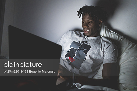 Young man with short dreadlocks lying in bed at night, looking at laptop. - p429m2201945 by Eugenio Marongiu