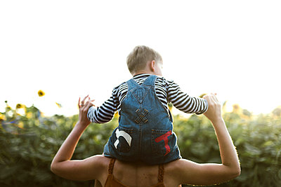 Back view of a son sitting on mother's shoulders amidst sunflower - p1166m2096571 by Cavan Images