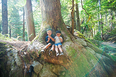 Two young explorers sit below old growth tree in natural forest. - p1166m2212593 by Cavan Images
