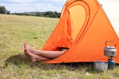 Young woman camps out in the meadow, city in background - p294m2207520 by Paolo