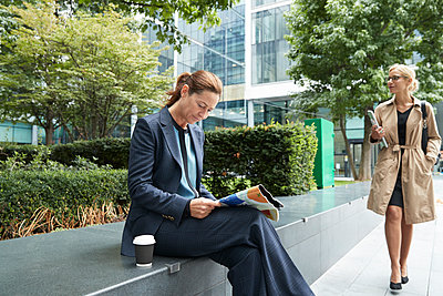 Businesswoman reading paper with colleague leaving after work at city - p300m2227071 by Pete Muller