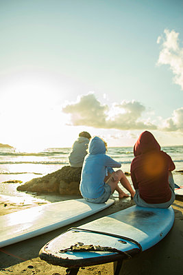 Three teenagers sitting on the beach watching sunset - p300m980838f by Uwe Umstätter