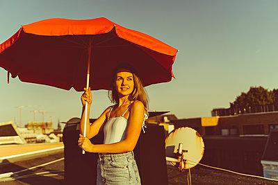 Junge Frau steht gut gelaunt auf Hausdach - p432m2219688 von mia takahara