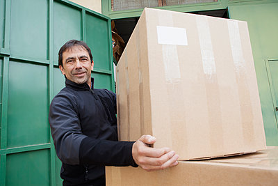 Mixed Race worker lifting cardboard box - p555m1491161 by REB Images