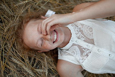 Smiling Caucasian girl with freckles laying in wheat - p555m1521373 by Vyacheslav Chistyakov