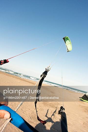 View of kitesurfing equipment and human hands holding it, Tarragona, Spain - p1166m2201457 by Daniel Santacatalina