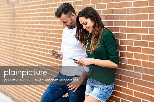 Couple looking at their smartphones at a brick wall - p300m2012653 von Javier Sánchez Mingorance