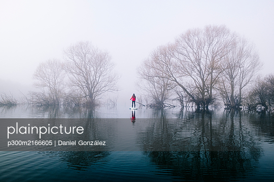 Young woman stand up paddle surfing on a lake in the fog - p300m2166605 by Daniel González