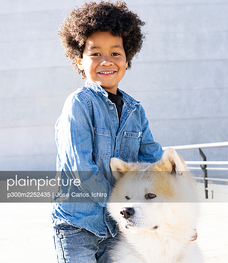 Boy with arm around dog smiling while standing outdoors - p300m2252435 by Jose Carlos Ichiro