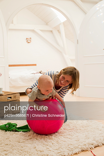 Mature mother and baby daughter on top of exercise ball in sitting room - p429m958567f by Christine Schneider