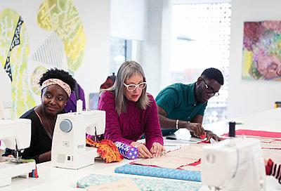 Fashion designers working in studio - p1023m2073992 by Sam Edwards