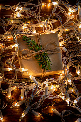 Christmas present amongst fairy lights - p1427m2163695 by Tetra Images