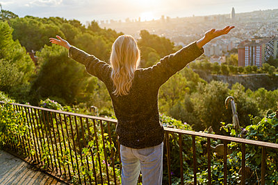 Rear view of carefree young woman standing above the city at sunrise, Barcelona, Spain - p300m2143755 by Giorgio Fochesato