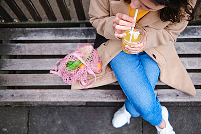 Woman drinking smoothie while sitting on bench - p300m2290465 by Angel Santana Garcia
