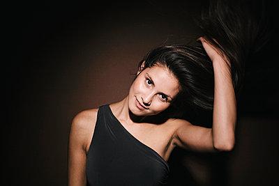 Junge Frau mit langen dunklen Haaren im Abendkleid - p586m953768 von Kniel Synnatzschke