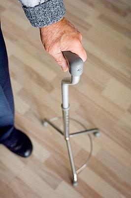 Senior man leaning on his walking stick - p8960692 by Theo van Pelt