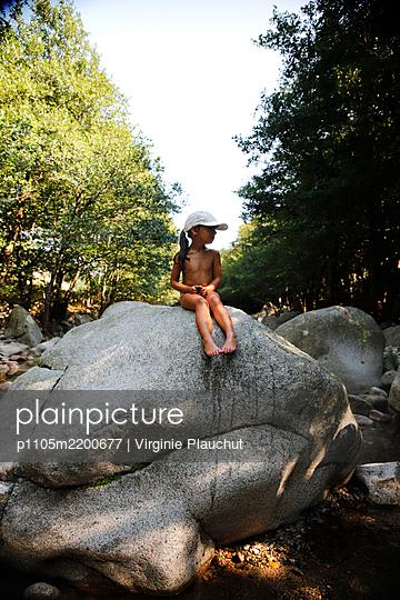 Little girl sitting on a rock - p1105m2200677 by Virginie Plauchut