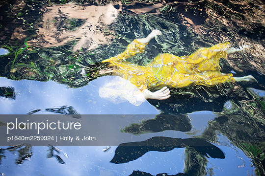 Woman in yellow dress swimming in lake - p1640m2259924 by Holly & John