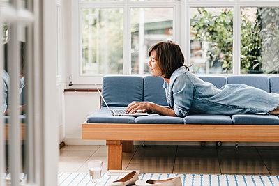 Reife Frau entspannt mit Laptop auf Sofa - p586m1178375 von Kniel Synnatzschke