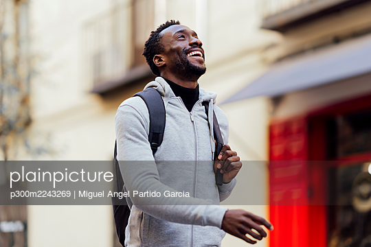 Smiling man carrying backpack while walking outdoors - p300m2243269 by Miguel Angel Partido Garcia