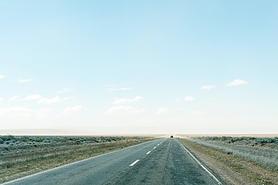 Driving along a remote flat road in Argentina on a sunny winter day. - p1166m2095237 by Cavan Images