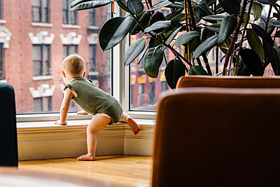 Curious toddler baby girl looking out of window in city - p1166m2285627 by Cavan Images