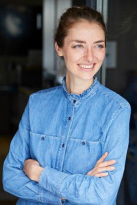 Portrait of smiling woman wearing denim shirt leaning against open window - p300m1581432 by Philipp Nemenz