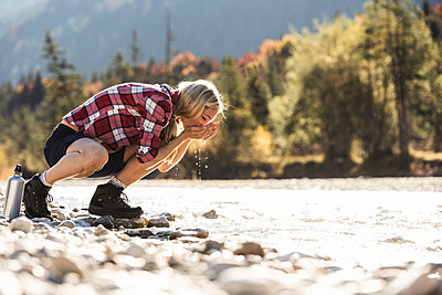 Austria, Alps, woman on a hiking trip having a break at a brook - p300m2081523 by Uwe Umstätter