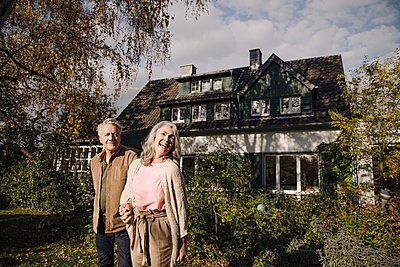 Happy senior couple in garden of their home in autumn - p300m2155221 by Gustafsson