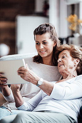 Senior woman using digital tablet while relaxing by granddaughter at home - p300m2274910 by Gustafsson