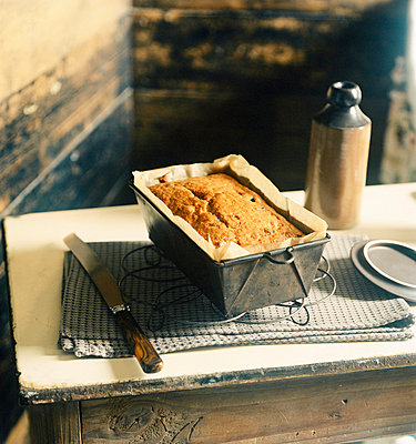 Freshly baked loaf cake in a tin on a tabletop - p349m695143 by Emma Lee