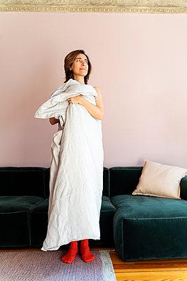 Frau hält sich Bettdecke am Körper - p432m2168900 von mia takahara