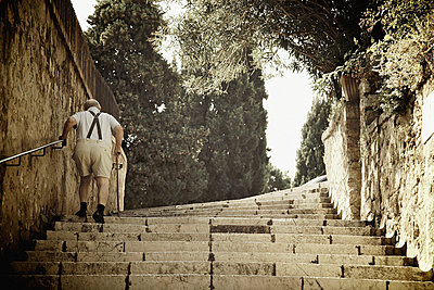 A senior man walks up steps; cannes provence france - p442m717877 by Patrick Swan